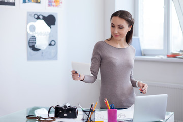 Attractive female photographer is working in her office