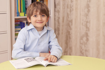 Cute сaucasian boy in blue shirt sitting at the table