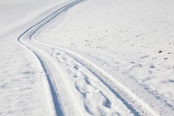 Car tire track and footprints on winter road