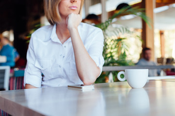 Woman with cup of coffee and mobile phone