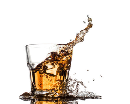 Glass of whiskey with splash, isolated on white background