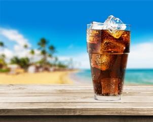 Poster de jardin Bar Glass of cola soda drink against tropical background