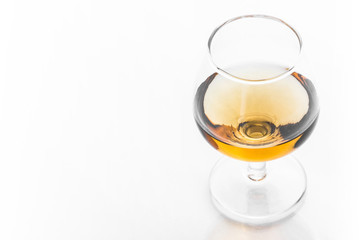 The cognac glass with golden brown alcohol inside.