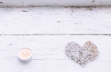 White handmade paper heart on old window and candle