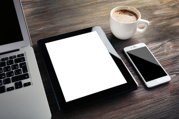Modern laptop, mobile phone, tablet and coffee cup on wooden table, close-up