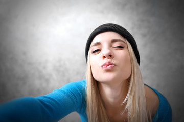 Young girl in black hat taking photo of her self on grey wall background