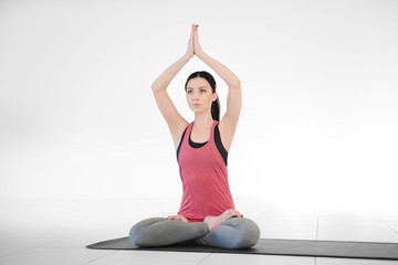 Young attractive woman does yoga in the class