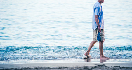 海岸を寂しく歩く中年の男性