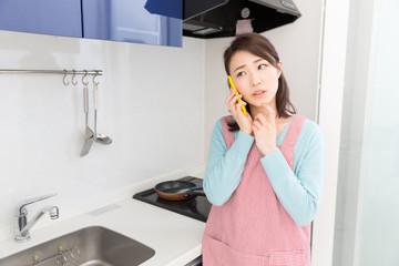キッチンで電話をする女性 考える