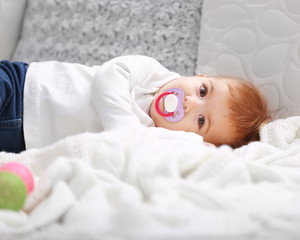 Sweet baby girl with a soother lying on white blanket