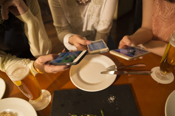 Three women have seen the smartphone during a meal