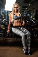 Blond slim fitness woman in grey sportswear.