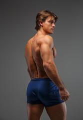 Shirtless muscular man in shorts.