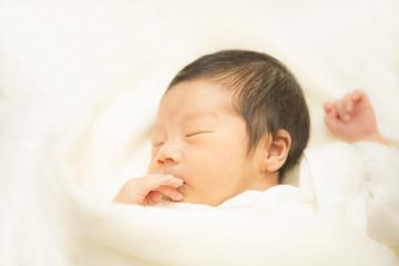 タオルに包まれて眠る新生児