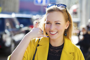 Beautiful happy blonde woman making a call me gesture