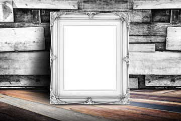 Blank white vintage photo frame leaning at plank wood wall and d