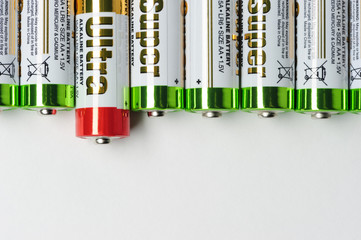 Batteries, row of alkaline battery AA size format with green top and one with red top, energy abstract background, selective focus
