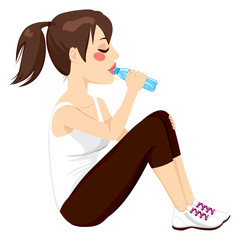Beautiful brunette woman drinking a bottle of water while resting sitting