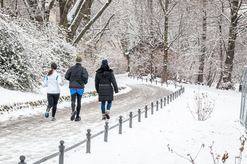 people walking and running by the river in the snow