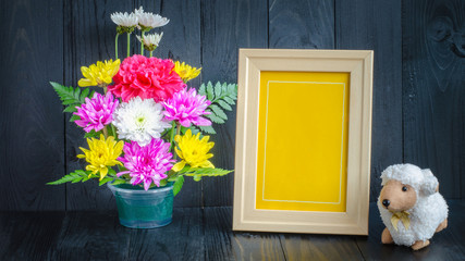 still life of frame picture and colorfull flower on black wooden