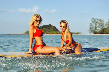 Surfer girls having fun on a surfboard in the sea