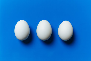Three white egg on the blue background
