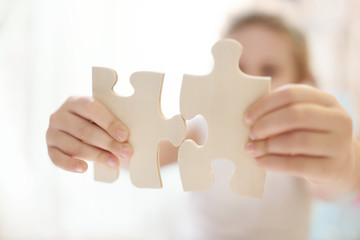 Child girl holding  two big wooden puzzle pieces. Hands connecting jigsaw puzzle. Close up photo with small dof. Education and learning concept.