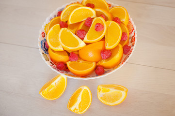 A large plate of sliced oranges and raspberries on white table. Slices of orange and some raspberries on the table.