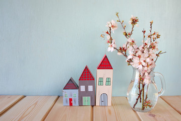decorative house next to white spring flowers. selective focus