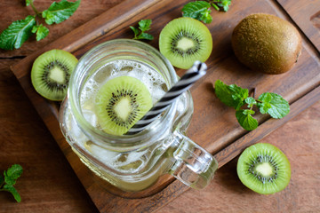 kiwi soda and mint in a glass on a wooden background.