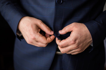 correct button on jacket, hands close-up, dressing