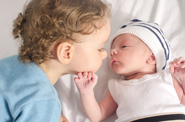Big brother kissing his little sibling. Loving toddler with his new born baby boy brother.