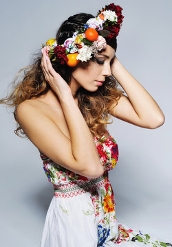 Beauty portrait of a gorgeous woman with gipsy hairstyle wearing handmade fairy flower crown .