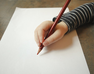 Child's hand holding a red pencil on a white sheet of paper. The child learns to write.