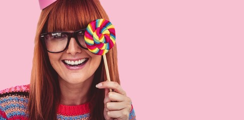 Composite image of hipster woman with lollipop and hat party
