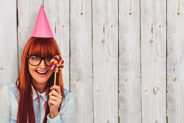 Composite image of hipster woman with hat party and lollipop