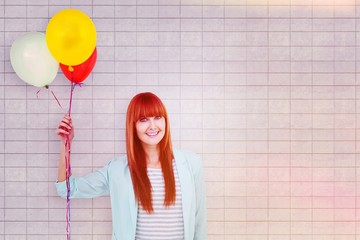 Composite image of smiling hipster woman holding balloons
