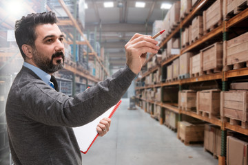 Young businessman checking inventory in a large warehouse