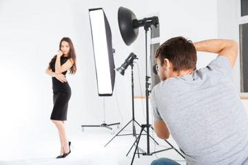 Man shooting female model in studio