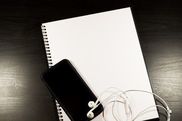 Blank notebook and smartphone with pencil on wooden table. The view from the top