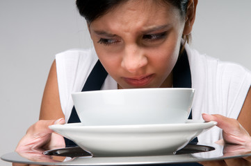 Young woman holding a plate of soup