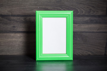 Empty photo frame on wooden background