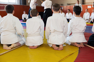 Foto op Aluminium Vechtsport Children in kimono sitting on tatami on martial arts seminar. Selective focus