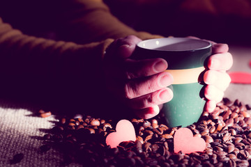 Female hands hold a coffee cup with beans