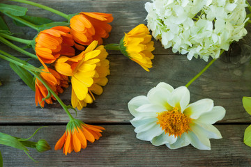 Yellow, orange and white flowers on gray old wooden table