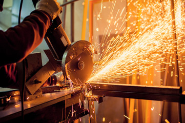 Electric grinder / A man working with electric grinder tool  on steel structure in factory, sparks flying
