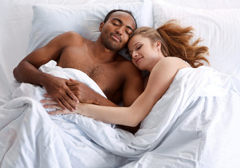 Young couple sleeping on the bed in bedroom. Concept of cheerful American family