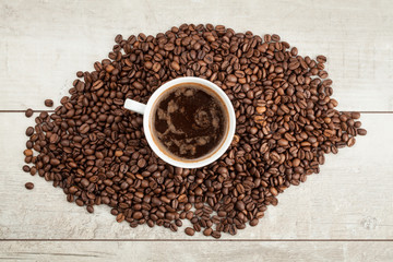 Cup of coffee in the coffee beans