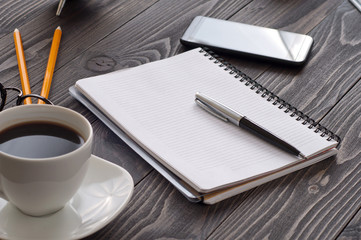 open notepad with blank pages, pen and cup of coffee