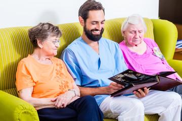 Altenpfleger schaut Fotos mit Senioren im Altenheim an